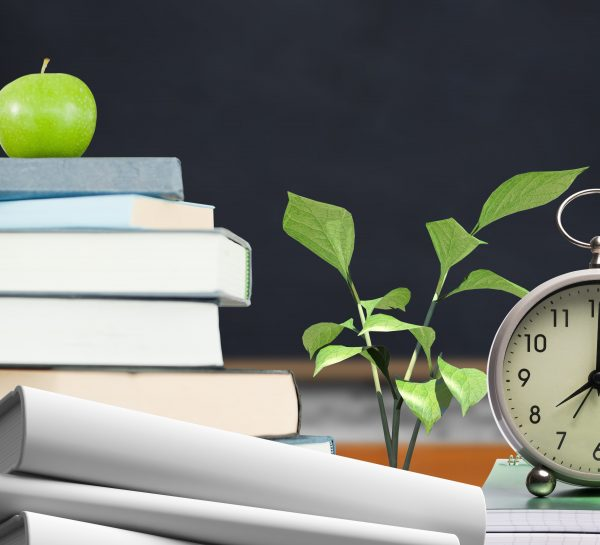 Apple and alarm clock over pile of book in the classroom