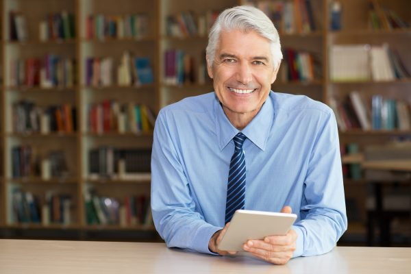 Smiling senior businessman using digital tablet